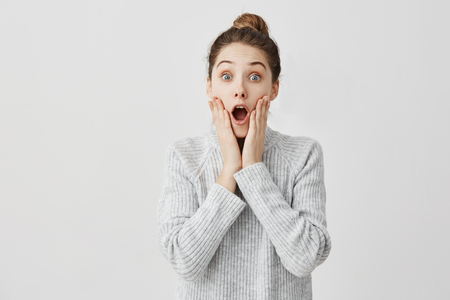 Attractive woman looking on camera with open mouth being shocked. Female student grabbing face being astonished about exam result. Education concept 免版税图像
