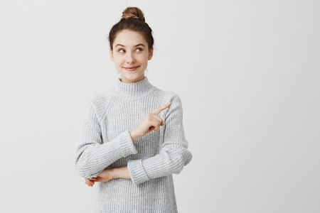 Pretty brunette woman posing on camera with tricky look and gesturing to side. Female designer presenting lovely product with index finger. Gesture concept Stock Photo