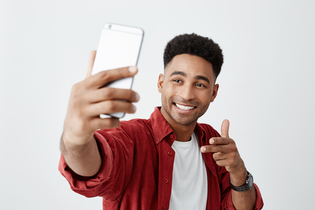 Say cheese. Close up of young beautiful dark-skinned man with afro hairstyle in casual white t-shirt and red shirt smiling with teeth, holding smartphone, making selfie photo. Stock Photo