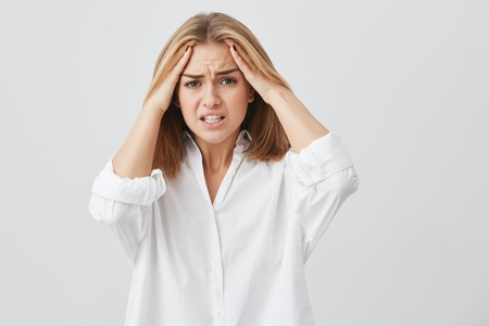 Frustrated young woman having terrible headache keeping hands on head frowning her face with pain looking unhappy and stressful. Female student in despair having stressful situation at university. Stock Photo
