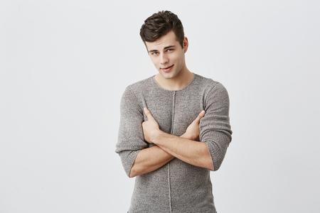 Retrato de hombre guapo serio con expresión atractiva, mantiene los brazos cruzados, trata de ser estricto. Muscular ajuste elegante estudiante masculino insatisfecho con la marca final, exige volver a tomar el examen