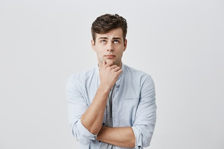Puzzled thoughtful male student dressed in light blue shirt, holding hand under his chin, frowning face, looking upwards, being dissatisfied with problems at university, thinking over his mistakes. Stock Photo