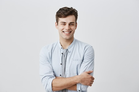 People and lifestyle concept. Attractive young caucasian male in good mood, in blue long sleeved shirt smiling cheerfully showing perfect white teeth, happy with positive news, keeping arms folded.