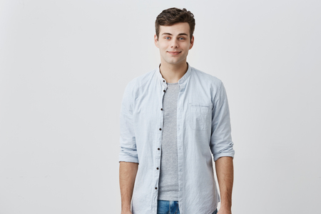 Cheerful pleased caucasian guy with blue eyes and dark hair dressed in elegant blue shirt smiling in good mood while posing in studio against gray background. Facial expressions concept