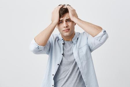Portrait d'un Européen fatigué, agacé, désespéré, fronçant les sourcils, mettant ses mains sur sa tête, se rappelant qu'il avait oublié quelque chose. Expressions de visage humain négatif, des émotions et des sentiments Banque d'images