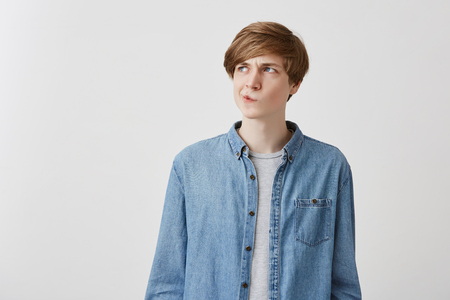 I dont know. Doubtful caucasian young male wearing denim shirt, pouting lips and looking up with indecisive expression on his face, showing doubt and hesitation. Body language and face expression