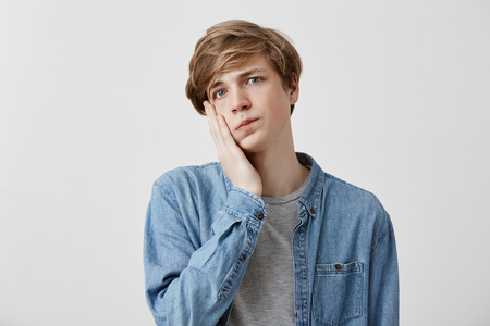 Headshot of stupefied upset young man wears denim shirt keeps hand on cheek, says: Omg, I am tired of that. Shocked Caucasian male realizes his fault. Negative feelings and emotions