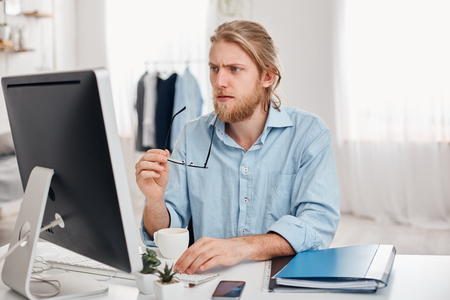 Serious concentrated pensive male businessman in blue shirt holds spectacles in hand, works on computer, thinks about financial report. Bearded manager or freelancer drinks coffee, generates ideas