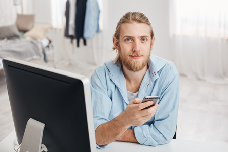 Bearded good-looking male office worker with gentle smile reads notification on smart phone, sits in front of screen at coworking space with cell phone, sends feedback to coworkers, browses internet Stock Photo