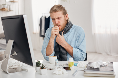Portrait of ill sick bearded male manager coughs, has cold and flu. Young fair-haired man has running nose, cough and bad cold, sits at workplace in front of computer screen. Illness and infection