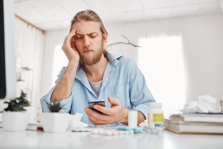Bearded fair-haired male office worker looking unhappily at screen of smartphone, leaning on his elbow, sitting at table in front of screen during hard working day. Manager suffers form headache.