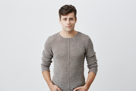 Displeased discontent european male frowns face, dislikes something, looks with disgusting expression, isolated against gray background. Stock Photo