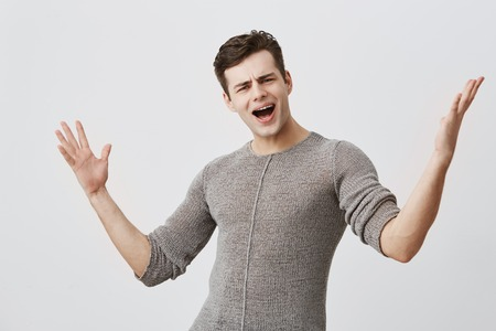Dissatisfied young male with dark hair closes eyes and screams loudly, gestures, being very emotional after passing exam, isolated against gray background. Stock Photo