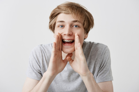 Stunned overjoyed caucasian male student screams with excitement, keeps hands near mouth, being glad to enter university or college. Emotional happy surprised young fair-haired man yells wow or omg Archivio Fotografico