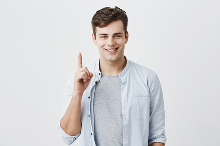 Satisfied and pleased caucasian customer pointing with index finger up at blank space over head for your advertisment. Good-looking positive man smiling with teeth and gesturing, posing at studio Stock Photo