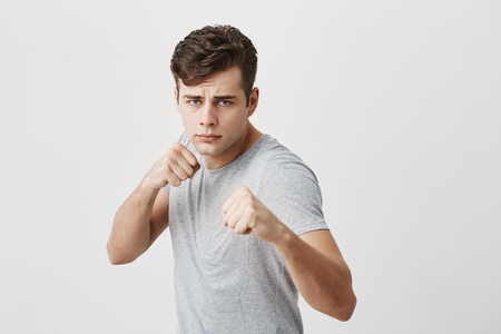 Serious confident muscular young sportsman frowns face in displeasure, shows clenched fists, demonstrates strength and irritation, ready to defend himself. Power and strenght concept. Stock Photo