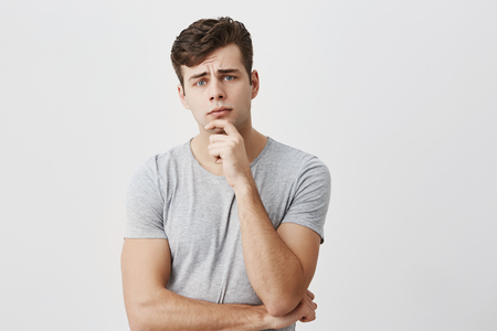 Horizontal portrait of handsome young male dressed casually keeps hand under chin, frowns his face, looks puzzled, listens to someone`s official speech, analyzes information. Peope and lifestyle Imagens