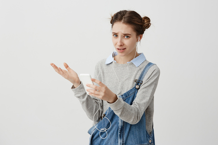 Upset trendy girl looking on smartphone with regret gaze and pursed lips. Brunette woman cant find favourite music in her gadget trying to upload it. Technics concept 스톡 콘텐츠