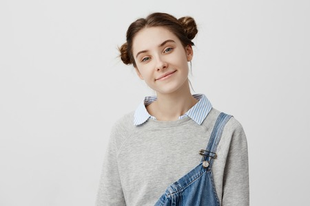 Close up portrait of lovely teen girl having clean skin looking on camera with kind smile. Shining brunette woman with hair in double buns feeling good enjoying her youth. Beauty concept Foto de archivo