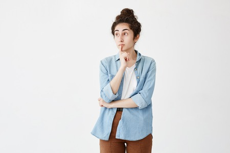 Thoughtful female with hair bun, keeps finger on lips, looks with pensive expression aside, in denim shirt and brown trousers. Young woman stares aside while making important decision 免版税图像