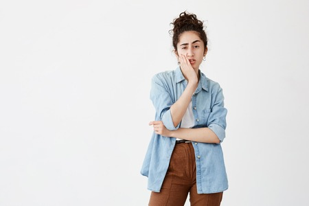 Troubled young woman with dark hair in bun in denim shirt touching her cheek and looking sideways with doubtful and sceptical expression, making important life decision, frowning face