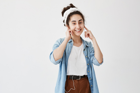 Music and technology concept. Dark-haired girl listening to audiobook or radio on cell phone with earphones, looking and smiling at the camera against white copy space wall for advertising content Stock Photo
