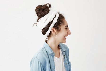 Profile of beautiful young woman in do-rag and trendy denim shirt, relaxing indoors, looking away with pretty smile, posing against white background with copy space for text or advertising content