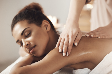 Attractive african girl having massage relaxing in spa salon. Closed eyes.
