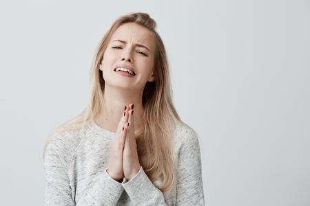 Superstitious religious praying beautiful woman with blonde straight hair, crying, pressing palms together for good luck, hoping wishes will come true, having excited look. Human emotions, feelings Stock Photo