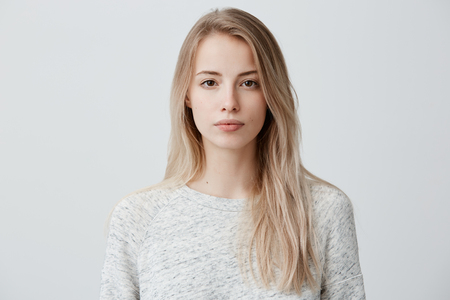 Confident good-looking beautiful woman with blonde dyed hair with healthy pure skin dressed in casual clothes looking seriously at camera. Youth and beauty concept Archivio Fotografico