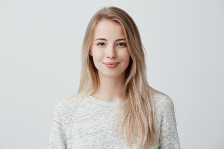 Śliczna, radośnie uśmiechnięta kobieta o jasnych włosach, ubrana niedbale, patrząc z satysfakcją na aparat, szczęśliwa. Studio strzałów z przystojny piękna kobieta odizolowane od pustej ściany studio. Zdjęcie Seryjne