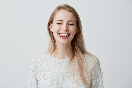 Gloomy young blonde woman with dyed hair dressed casually making faces at camera, blinking, sticking out her tongue. Positive girl having fun indoors Stock fotó