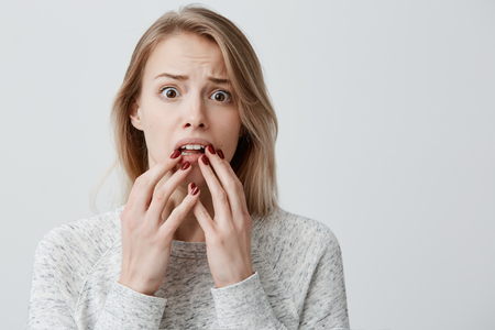 Surprised amazed attractive young blonde with dyed hair female wearingsweater having astonished face expression, covering her open mouth with hands, looking at camera in shock and full disbelief