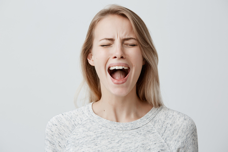 Emotional blonde woman opening her mouth widely screaming loudly being dissatisfied with something expressing disagreement and annoyance. Female shouting at boyfriend, Negative emotions and feelings Stockfoto