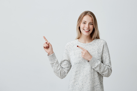 Check this out. Attractive positive young female with dyed blonde hair smiling cheerfully and pointing with forefingers away, indicating copy space on blank wall, having joyful happy look Banque d'images
