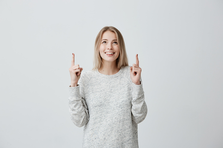 Joyful blonde girl wearing long sleeved sweater looking upwards, pointing fingers at copy space above her head. Caucasian beautiful woman indicating something on blank studio wall with hands