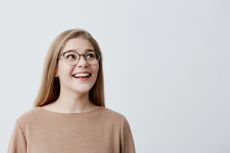 Happy excited surprised female model with blonde straight hair in glasses, being pleased with something, can`t believe in her success, glad to be praised, poses against gray studio background