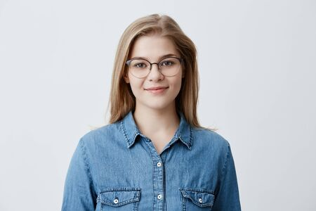 Horizontal portrait of smiling happy young pleasant looking female wears denim shirt and stylish glasses, with straight blonde hair, expresses positiveness, poses against gray background