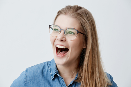 Excited blonde female wearing glasses, denim shirt, exclaims joyfully, happy to find out about enrollment to university, dreams to become student for long time, can`t believe in success.