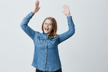 Overjoyed female wears danim shirt, stylish eyewear, gestures in excitement, exclaims loudly in astonishment, being glad to meet old friend, raises arms up. Blonde female rejoices success at work.