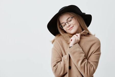 Dreamful positive female in retro outfit, wraps in coat, stands against gray background with closed eyes, imagines something pleasant, tries to relax. Positive human emotions and feelings concept
