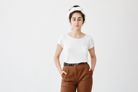 Cute pretty teenage girl wears loose white t-shirt and brown trousers, holds her hands in pocket, feels enjoyment. Pleasant-looking girl posing against white background