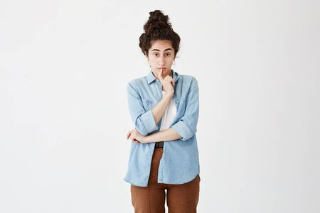 Pensive female with dark hair in bun thinks about solving problem, keeps finger on lips, tries to predict ways out, looks at camera, poses against white background with copy space for advertisment
