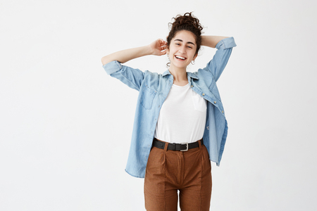 Happy cheerful young woman wearing her dark hair in bun rejoicing at positive news or birthday gift, joyfully and charmingly smiling. Positive student girl relaxing indoors after college
