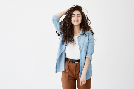 Portrait of cheerful brunette with long wavy hair, dressed in denim shirt and brown trousers, glad to recieve good news, Student girl smiles broadly, rejoices life, expresses positive emotions Stock Photo