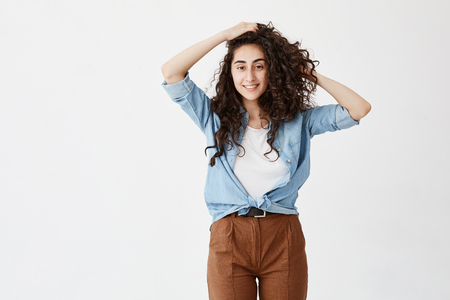 Pleasant-looking positive girl wears brown trousers and denim shirt, looks happily at camera, smiles broadly, rejoices youth, plays with curly hair. Female poses against white backgorund