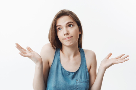 I dont know, sorry. Attractive funny dark-haired caucasian girl in casual clothes looking aside with awkward expression, spreading hands. Woman pretending she dont know anythting about others man t-shirt in house. Banque d'images
