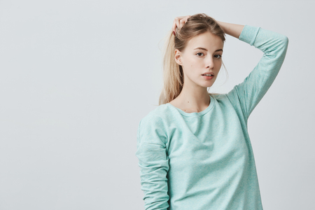 Portrait of good-looking young woman with oval face, dark eyes and fair straight hair wearing blue casual sweater, playing with her hair, pensively and confidently looking at camera
