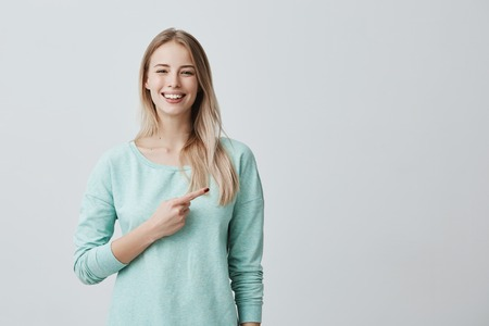 Advertising concept. Smiling cheerful positive european woman wearing light blue shirt pointing her index finger aside at copy space for promotional text, motivating and attracting customers.