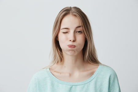 Portrait of frowning blonde young woman dressed in light blue sweater, pouting her cheeks, blinking, doesn`t want to share information. Human emotions, face expression, reaction and attitute
